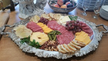 Cheese and charcuterie board made with imported and domestic cheeses, cured meats, fruit, nuts and cornichones.
